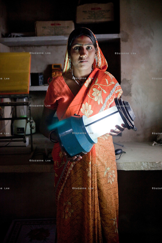 Santosh Devi, aged 19, poses for a portrait in her workshop at home. She graduated 2 years ago from the solar engineering course of the Barefoot College in Tilonia, Ajmer, Rajasthan, India. She has since solar powered 20 homes in her village, Balaji Ki Dhani, Bauli, Nagur District, Rajasthan, making it the first village in India to be 100% solar powered in all houses. Above this, she does all maintenance for the neighbouring village, Gudda Ki Dhani, where the previous male solar engineer had left the village to find unrelated work in the city. Barefoot College prefers training women to be solar engineers for this reason that they have higher chances of staying in the village instead of moving to the cities. Photo by Suzanne Lee for Panos London
