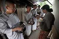 "A Buddhist woman offers charity and prayers to the Mae Chees clad in white robes as they stand silently in the early morning light, holding out their alms bowls hoping for food or monetary offerings. Vanished by centuries the lineage of ""Bhikkhu?nii"" (Order of Nuns) has been brought to the ongoing Thai society's debate. White-clad thai nuns, who keep the eight precepts and have their heads and eyebrows shaved are known as the lon-existing ""mae chees"" (low category to call the lay nuns). Females who have turned to religous life, as renunciants, live ostracized and marginalized by the Sangha (Buddhist community) and Thai society, denying them full access to the monastic life as well as rights and support from the government. Today nunhood is not recognized by any asian country belong to the Theravada Buddhist order. Most of the eight precept holders live in temples run by male abbots, at the shadow of the monks; with the exceptional existence of a few para-monastic institutions as the Sathira Dhammasathan meditation centre, where ""mae chees"" are not allow to held a temple, but not denied to practice the spiritual life."