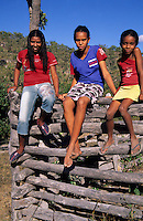 Country girls sitting on corral fence, Chapada da Piteira, Brazilian Highlands, Goias, Brazil