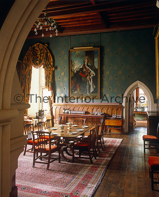 The grand dining room is decorated with a blue and gold wallpaper and a large portrait