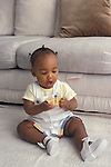 Richmond, CA African American baby twelve months old demonstrating ability to grasp a block in each hand and bang them together  MR