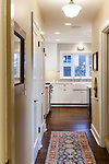 View down the hallway from the master bedroom to a newly remodeled kitchen with crisp white cabinetry and dark wood floors