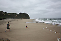Daddy chases son on the sands of Pomponio State Beach on the California coast.