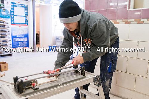 Tiling student using the tile cutter, Able Skills, Dartford, Kent.