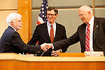 New councilmember, John Harpootlian, is greeted by councilmembers Gary Waldeck and Rich Larsen.
