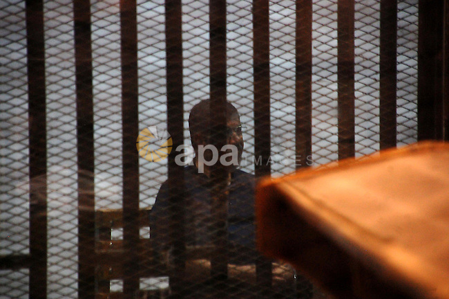 Former Egyptian President Mohamed Morsi sits inside a defendant's cage during his trial in Cairo, Egypt on May 24, 2015. Cairo Criminal Court resumed Sunday the espionage trial of ousted president Mohamed Morsi and 10 co-defendants over charges of leaking to a foreign country, namely Qatar, top secret military reports pertaining to Egypt's Intelligence Authority and Armed Forces and related to the country's national security. Photo by Stringer