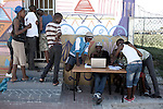 Khayelitsha, South Africa March 5, 2013: Boys come to register at Amandla EduFootball which was founded by Jakob Schlichtig, Florian Zech outside the field in Khayelitsha a poor township outside Cape Town, South Africa. They use football to initiate, support educational projects for youth in the township. The program keep children busy and it decreases the risk of them joining gang, criminal activity or teenage pregnancy. The crime level has decreased substantially in the area since the program was created in 2006. (Photo by: Per-Anders Pettersson)