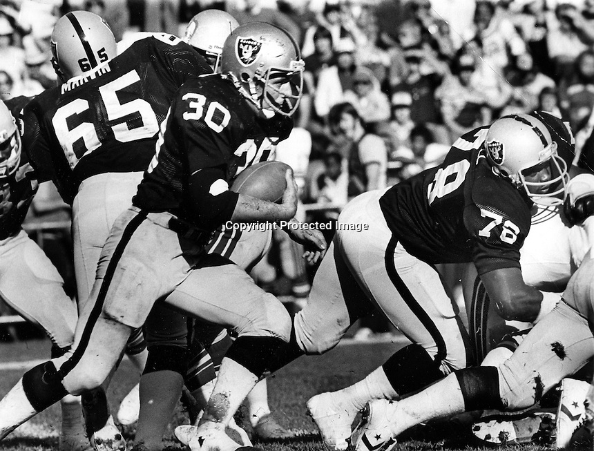 Oakland Raiders Mark Van Eeghen with blocks from #65 Mickey Marvin and #76 Art Shell. (1980 photo by Ron Riesterer)