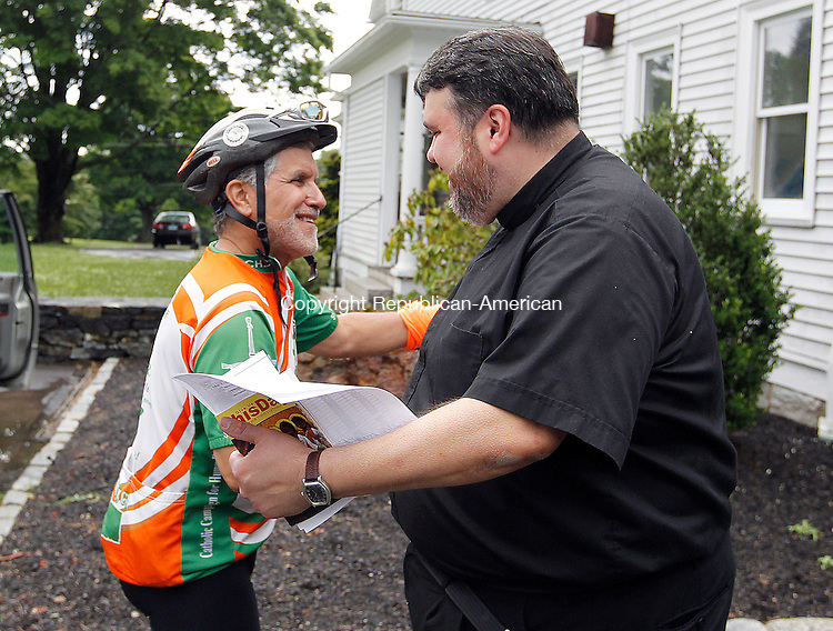 """Middlebury, CT-25 June 2012-062512CM01-  Lou Terzo (left) of Manchester is welcomed by Father Dennis Vincenzo (right) of St. John of the Cross Parish Monday afternoon in Middlebury.  The """"Brake the Cycle"""" team, a group of men and women who cycle for a week each summer to raise awareness for poverty issues, stopped by the parish house during the journey.  Father Vincenzo opened up the house for the team to stay.     Christopher Massa Republican-American"""