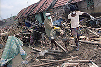 Government workers removing a dead body from the debris near Nagapattinam.India.
