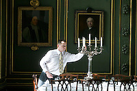 Servery Assistant, Sebastian Matusik, demonstrates for the photograph how he lines up the candlesticks for the evening's formal dinner at Magdalene College in Cambridge, United Kingdom, 11 March 2007.