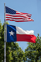 U.S. and Texas flag on a flag pole flying in the breeze of the Lone Star State.