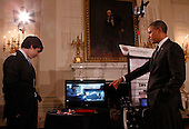 United States President Barack Obama watches a video with Benjamin Hylak of West Grove, Pennsylvania, who built an interactive robot, while touring student science fair projects on exhibt at the White House in Washington, D.C. on February 7, 2012.  Obama hosted the second White House Science Fair celebrating the student winners of science, technology, engineering and math (STEM) competitions from across the country. .Credit: Molly Riley / Pool via CNP