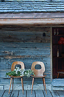 A pair of chairs has been placed on the weathered wooden decking beyond the open door to the chalet
