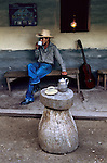 HONDURAS-10014NF2; Honduras; Latin America. A man drinks tea outside a house.