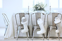Christmas stockings hang on the backs of metal chairs surrounding a laid dining table
