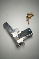 Handgun amd bullets on white seamless