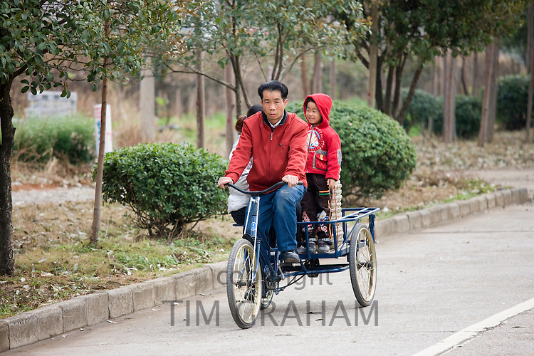 Family on a tricycle in Guilin, China. China has a one child family planning policy to reduce population.