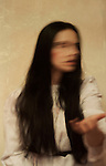 blurry atmospheric and ghostly image of a young woman with closed eyes and long black hair standing with hand turned towards camera