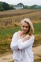 Blonde woman in white shirt standing in front of field