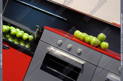 Stylish kitchen interior design in bright red colors with green apples on a table