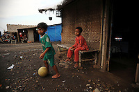 Children play outside their makeshift home not far .from Besuki village, which has been overwhelmed by mud. Since May 2006, more than 10,000 people in the Porong subdistrict of Sidoarjo have been displaced by hot mud flowing from a natural gas well that was being drilled by the oil company Lapindo Brantas. The torrent of mud - up to 125,000 cubic metres per day - continued to flow three years later.