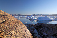 Icebergs and glacier polished bedrock at dusk along Sermilik Fjord near settlement of Tiniteqilaq, East Greenland