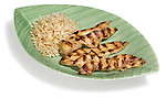 chicken strips and brown rice on a leaf plate
