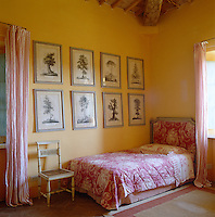 Red and white textiles in contrasting patterns are set against the traditional Tuscan yellow ochre of this bedroom wall