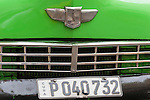 Havana, Cuba; the front license plate and grill of a neon green, classic Studebaker parked on the street in Old Havana