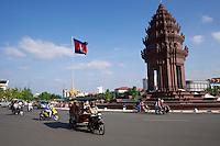 Phnom Penh, Cambodia.<br /> Motorbikes passing  Independence Monument.