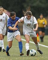 Boston College defender McKenzie Meehan (22) dribbles down the wing as Duke University defender Christina Gibbons (31) pressures.Boston College (white) defeated Duke University (blue/white), 4-1, at Newton Campus Field, on October 6, 2013.