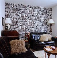One wall of the living room is covered in a bold botanical wallpaper