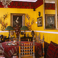 The dining room is furnished with 19th century Indian Sindh chairs, African masks, French wall lights and a romantic Spanish portrait