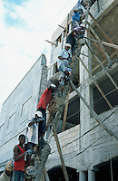 Haiti. Province of Ouest. Port-Au-Prince. Downtown. House under construction. Workers, earning one us dollar a day, are all on the same ladder. They carry hand to hand buckets of concrete to the roof. © 2003 Didier Ruef