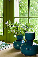 A pair of contemporary ceramic vases have been placed on the window sill of the library