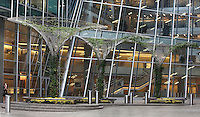Woman smoking outside a buiding with metallic structures in the shape of a palm tree and with climbing plants inside, Canary Wharf, West India Docks on the Isle of Dogs, Borough of Tower Hamlets, East London, UK. Picture by Manuel Cohen