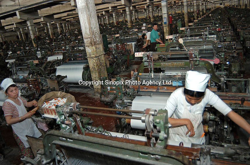 Workers work with the textile machinery at a textile factory in Zhengzhou, China.
