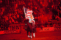 Niki Flundra of Rockyford, Alberta, Canada bears the American flag during the National Anthem at RodeoHouston in 2014.