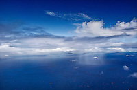 A breathtaking aerial view of a small rain cloud on the Pacific Ocean, with O'ahu in the distance