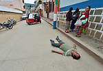 A drunk man lays in the middle of the street in Comitancillo, Guatemala.