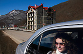 A woman stares out of a car window in front of an unfinished hotel in Russia's Black Sea coastal city of Sochi. ..The resort, perched on the foot of snow-capped mountains, is bidding to host the 2014 Winter Olympics.  Billions of dollars are poured in to the area, creating a construction boom.