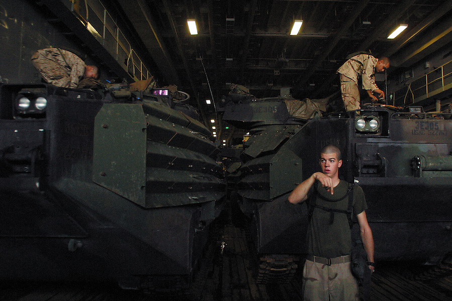 The Marines of the 11th's Amphibious Assault Vehicle Platoon prepare to launch their vehicles for the partially-submersible lower deck of the USS Denver. The vehicles, known as AAV's or amtracks, convert from lumbering watercraft to armored personnel carriers when they reach the beach. Famously uncomfortable for their passengers, they saw a great deal of service during the invasion transporting Marines from Kuwait to Baghdad.