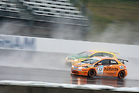 Gordon Sheddon and Darren Turner  BTCC Racing drivers racing in the wet at Rockingham curcuit, corby