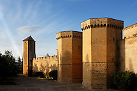 Oblique view of fortified wall and two polygonal towers, marking the entrance to the Monestir de Poblet, 1151, Vimbodi, Catalonia, Spain, pictured on May 20, 2006, in the evening. These fortifications were built  during the 14th century by the House of Aragon and are an impressive example of late gothic military architecture. They stand in contrast to the use of the Monastery as a place for prayer. The Monastery of Poblet belongs to the Cistercian Order and was founded by French monks. Originally, Cistercian architecture, like the rules of the order, was frugal. But continuous additions  including late Gothic and Baroque, eventually made Poblet one of the largest monasteries in Spain which was later used as a fortress and royal palace. Poblet was closed in 1835 by the Spanish State but refounded in 1940 by Italian Cistercians. It is a UNESCO World Heritage Site. Picture by Manuel Cohen.
