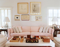 The living room is furnished with a large sofa covered in a pink-and-white candy stripe with a collection of framed drawings and prints displayed on the wall above