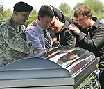 "Members of the McCrady family grieve for Marine Sgt. Jon ""J.J."" Bonnell Jr. at his burial service at Memorial Park Cemetery in Ft. Dodge, Iowa.    Bonnell was killed in Iraq in 2007."