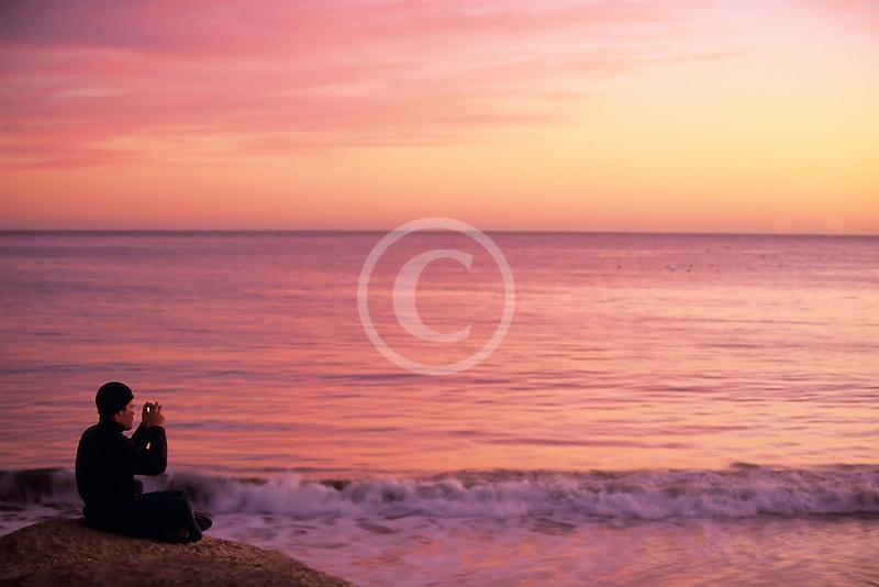 California, Santa Cruz, Man photographing at sunset