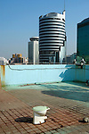 Abandoned toilet on the rooftop of a downtown apartment building, with office towers behind...Shenzhen, Guangdong 2004..China [sur]real©Mark Henley
