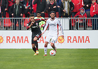 Toronto, Ontario - May 3, 2014: New England Revolution midfielder/forward Lee Nguyen #24 and Toronto FC midfielder Jonathan Osorio #21 in action during a game between the New England Revolution and Toronto FC at BMO Field.<br /> The New England Revolution won 2-1.